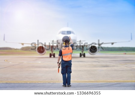 signal vest Aircraft. Airport officials are signaling the landing of the aircraft. #1336696355