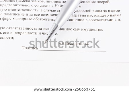 Signature of the contract with pen on paper with text.