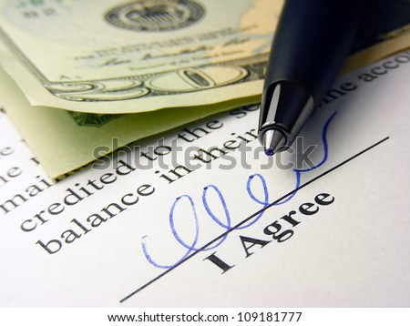Signature, pen and money on a contract text.