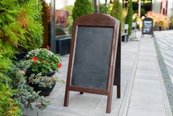 Signboard on the street. Empty menu board stand. Restaurant sidewalk chalkboard sign board. Freestanding A-frame blackboard near outdoor cafe. Copyspace for text, selective focus