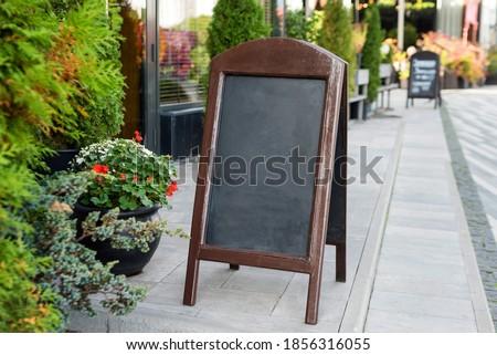 Signboard on the street. Empty menu board stand. Restaurant sidewalk chalkboard sign board. Freestanding A-frame blackboard near outdoor cafe. Copyspace for text, selective focus Stock photo ©