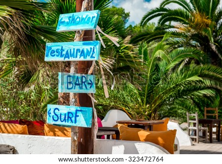 Signboard with arrows. Shower, bar, restaurant and surf directions on the Ibiza nudist beach. Balearic islands, Spain