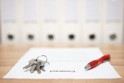 signed contract and keys of the property with documents  in background, concept of business  premise deal