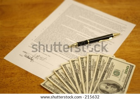 Signed contract with pen, and money on top. Bills denomination $100.