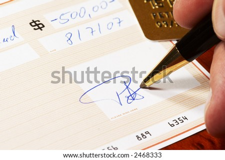 signing a bank check, gold credit card in background