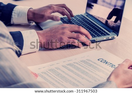 Signing a business contract. Two successful businessman smiling and looking at the laptop while businessmen sitting at a table working on a laptop on a gray background close-up view.