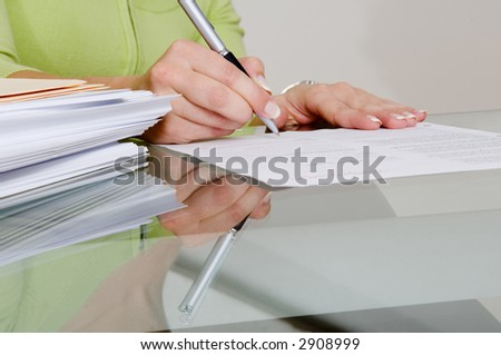 Signing beside a stack of papers.