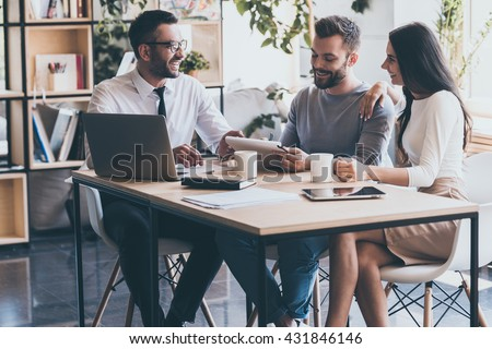 Signing good condition contract. Cheerful young man signing some documents while sitting at the desk together with his wife and man in shirt and tie