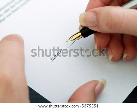 Signing of the contract by an ink pen with a gold feather