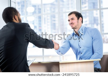 Signing of the contract. Two serious businessman sitting at the negotiating table in the office and shake hands. Business people dressed in formal wear