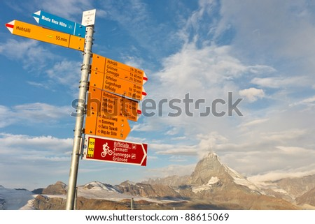 Signpost at Matterhorn, Switzerland, with directions to various hiking trails. - stock photo