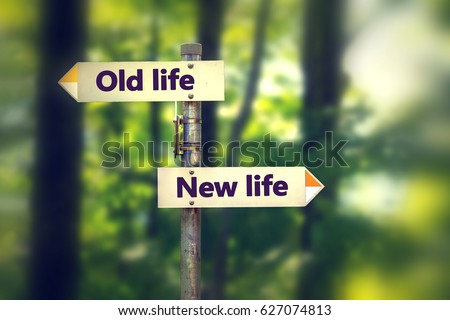 Signpost in a park with arrows old and new life pointing in two opposite directions #627074813
