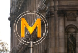 Signpost of the Metro Subway in Paris France at the Town hall of the first Arrondissement in Sunlight with spider webs marking the entrance to the underground transport system of the french captital