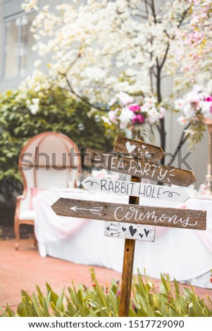 Signpost showing directions for alice in wonderland themed wedding