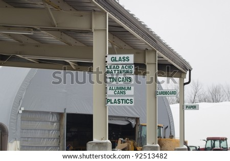 Signs at the recycling center directing where to put glass, lead acid batteries, aluminum cans, plastic, cardboard, tin cans, and paper.