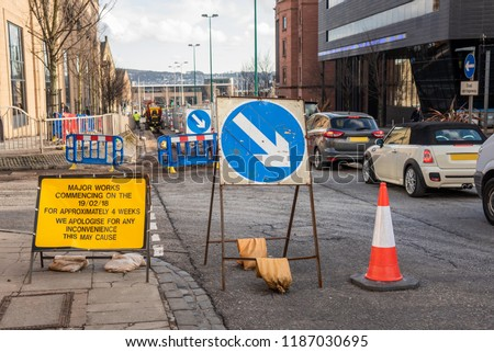 Signs, Barriers and Traffic Cones Partially Blocking a Busy Street Because of Roadworks in a City Centre