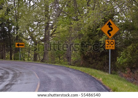 signs indicating a winding road and arrow indicating a sharp curve on a secondary road in the foothills of the Ozark Mountains