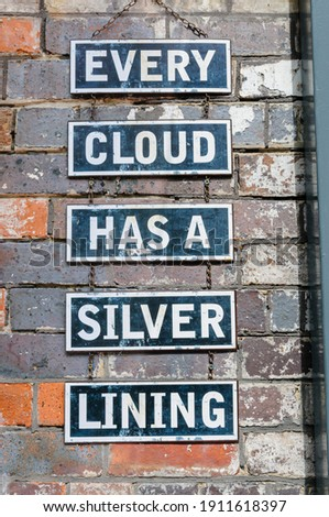 Signs on a brick wall saying 'Every cloud has a silver lining' ストックフォト ©
