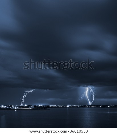 Signs - powerful lightning strikes over a lake in the city