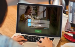 signup screen with blonde girl and pad against woman using laptop at office