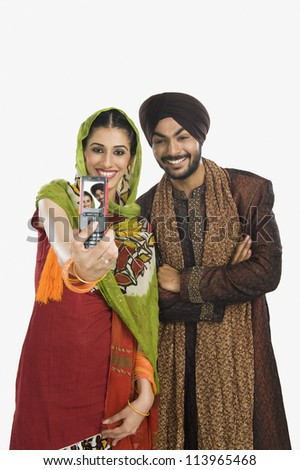 Sikh couple taking a picture of themselves with a mobile phone