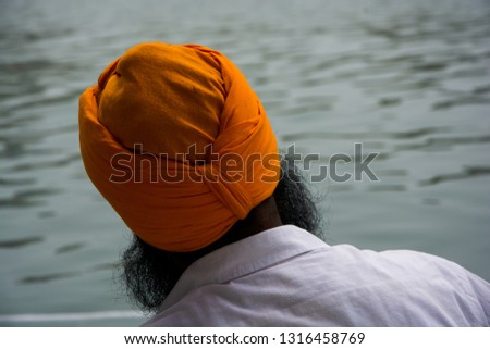 Sikh on his back wetting himself in the nectar lake of the Golden or Golden Temple of Amritsar or Harmandir Sahib. Sikhs India
