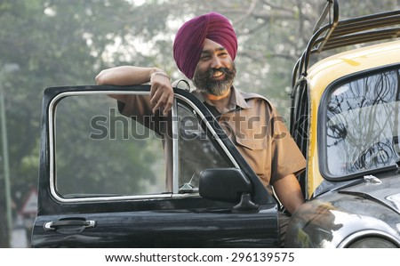 Sikh taxi driver standing next to his vehicle
