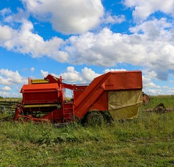 silage and forage harvesting equipment is standing on the edge of the field, waiting for work. A harvester near the field, before haymaking, and harvesting forage crops.