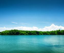 Silent lake under blue sky.