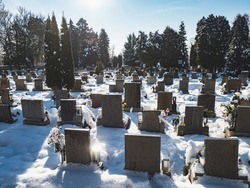 Silent snowy cemetry with headstones seen from behind in sunny winter day.
