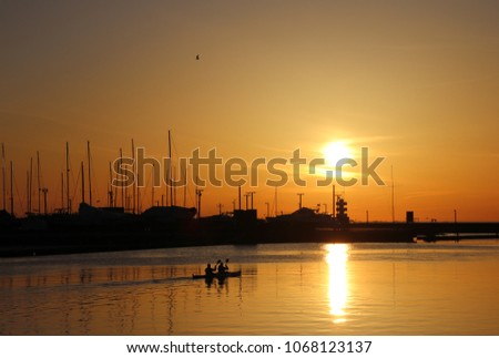 Silhoette of canoe with two people on water on sunset, with dark silhoettes of yahts/boats behind with red sky and low sun. #1068123137