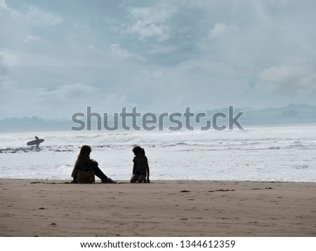 Silhoettes of mother, daughter and a serfer on a beach. Calm, peacefull atmosphere. #1344612359