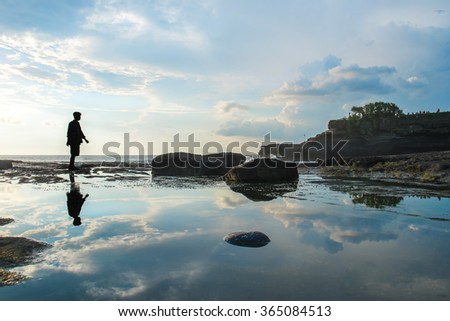 Silhouette a man walking with reflection on the water on the island