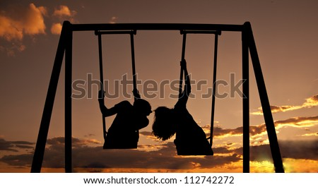 silhouette a pair of synchronous swinging on a swing and kissing in the evening on the background of a dramatic sunset sky