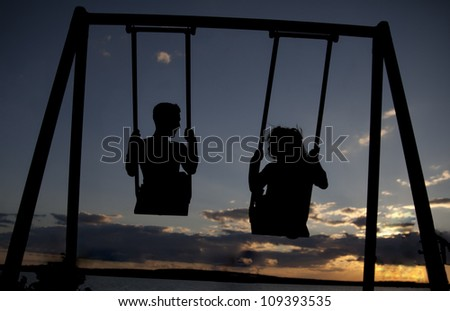 silhouette a pair of synchronous swinging on a swing in the evening on the background of a dramatic sunset sky