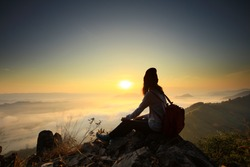 Silhouette A young woman site on the rock on top of cliff to see sun rise and sea of mist at Poo Pha Dak, Nong Khai Province of Thailand