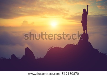 silhouette achievements successful arm up man is celebrating success with sunrise.Vintage color