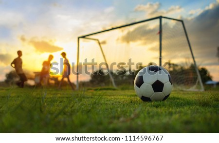 Silhouette action picture of a group of kids playing soccer football for exercise in community rural area under the sunset. For world cup trend concept.