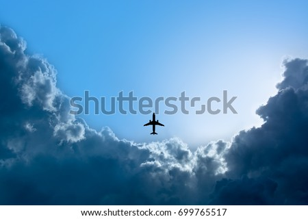 Silhouette airplane flying in blue sky with rain clouds and sunshine