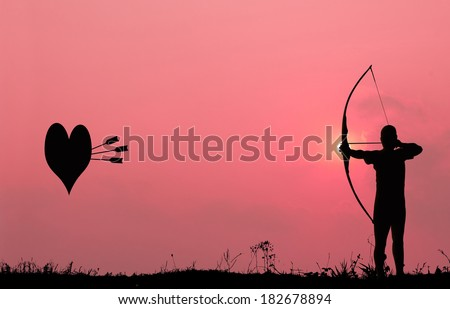 Silhouette archery with a bow shoots the arrows at the heart shape target in the pink sky and cloud.