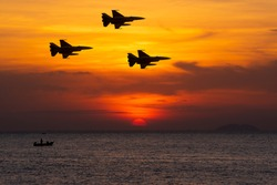 Silhouette army Show performant of air craft in air show with sun sky ocean view at sunset time background.