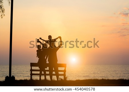 Silhouette Asian family standing selfie camera family consists of parents and children happy. The family enjoyed a holiday Holiday over blurred beautiful nature sea.Concept of friendly family.