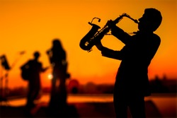 Silhouette autumn or summer scene of saxophone musician man showing with blurry jazz trio band and twilight or sunset city scape background. Image for happy new year party or celebration concept.