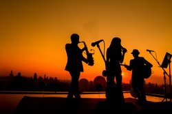Silhouette autumn or summer scene of 1 woman and 2 men trio musician before twilight time on sky. Trio band showing on sunset light background, Bangkok Thailand