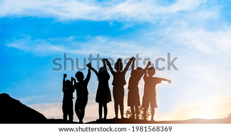 Silhouette back view refugee kid group  playing in sunset.Kid child boy and girl worship.Raised hands blessing praying worship, Hope, freedom, Diverse, Faith, Praise, world refugee day.Adoption kid.