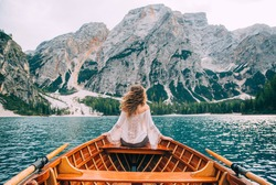 Silhouette back woman long hair flying fluttering wind, turned away face sitting in wooden boat. Tourist white blouse long sleeves enjoy nature Italian mountains alpine lake. river waves green forest