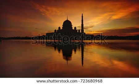 Silhouette Beautiful sunrise over the majestic mosque, Putra Mosque (Masjid Putrajaya). Soft focus due to slow shutter shot. #723680968