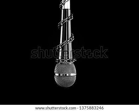 Silhouette black and white of microphone with a chain, depicting the idea of freedom of the press or freedom of expression on dark background. World press freedom day concept.