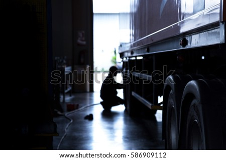 silhouette blur automobile mechanic checking truck in the garage, selective focus and cool tone photograph. #586909112