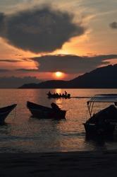 silhouette boat across the sunrise